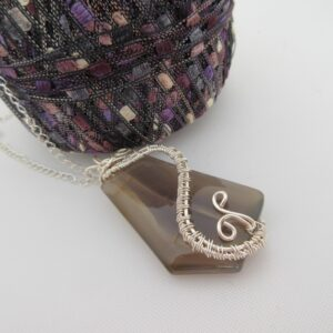 Pendant with large grey agate gemstone in irregular asymetric shape. Silver plated wire wrap detail. On silver plated chain