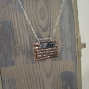Silver pendant in a rectangular tag shape with Pictish design and a sodalite gemstone, tube shaped. On a fine sterling silver chain