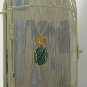 Pendant with green oval amazonite gemstone wire wrapped with gold plated wire and hanging from 18 inch gold plated fine curb chain