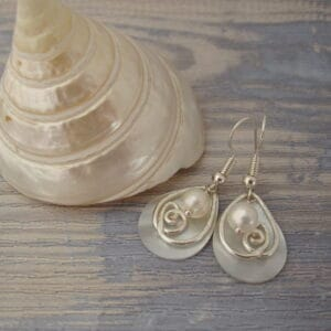 Silver plated earrings with tear drop shaped shell pearl, hammered silver plated wire detail and a single freshwater cultured pearl