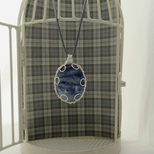 Large oval pendant featuring denim blue sodalite with a silver plated wire wrap. Hanging from grey cord 24 inches. One of a kind, designed and created in the Isle of Skye