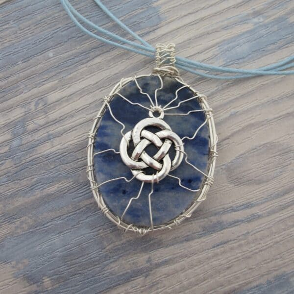 Back of oval sodalite pendant showing wire work with celtic knotwork. Silver plated wire. Hanging from grey cord 24 inches. One of a kind, designed and created in the Isle of Skye
