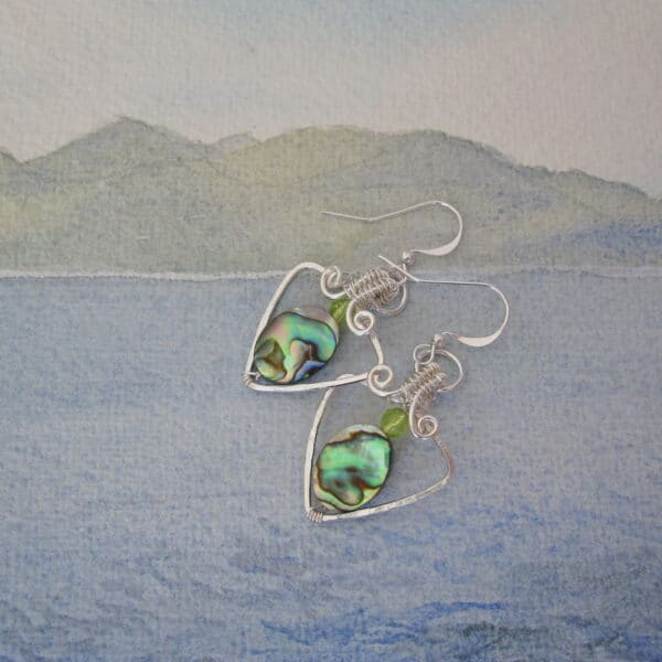 Silver plated earrings, triangular shape drop. With oval abalone shell and small faceted peridot above. One of a kind. Designed and created in the Isle of Skye by Indigo Berry