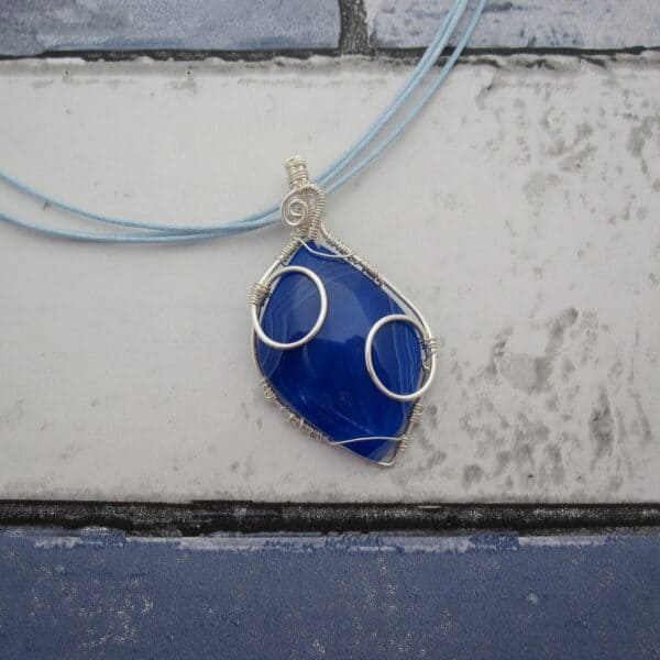 Bright cobalt blue agate pendant, diamond shaped with silver plated wire wrap detail. Hanging from a triple strand light blue cord, finished with silver plated clasp.