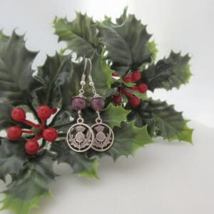 Drop earrings with silver coloured thistle charm and round purple jasper bead.